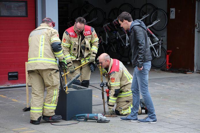 Brandweerlieden breken de in beslag genomen kluis open.