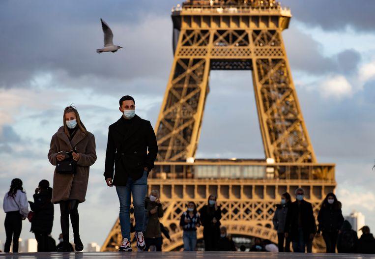 Mensen met mondmasker aan de Eiffeltoren in Parijs. Beeld EPA