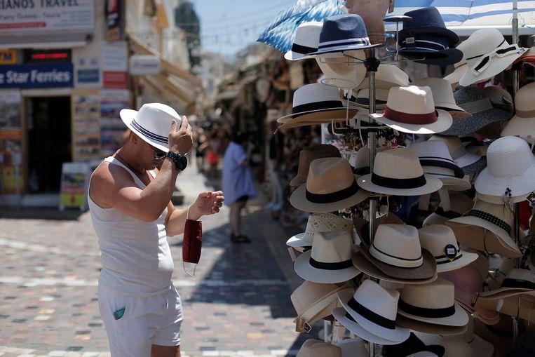 Een toerist probeert een hoedje uit in Athene. Beeld EPA
