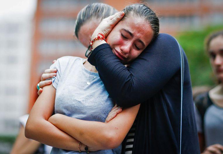 Brazilië: een meisje wordt getroost bij een herdenking van de aanslagen op het Franse consulaat in Sao Paolo Beeld AFP