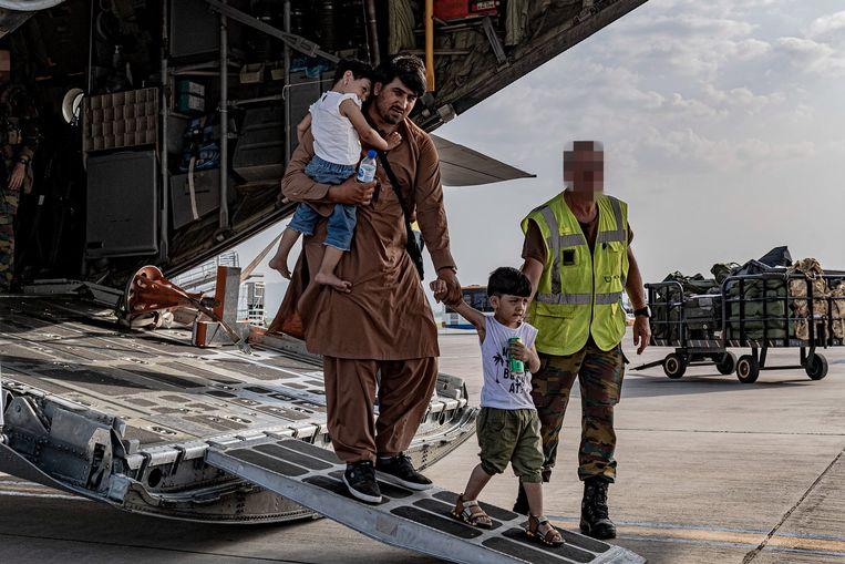 Een Afghaanse familie arriveert aan de luchthaven van Islamabad nadat ze door Belgische militairen geëvacueerd zijn uit Kaboel.  Beeld EPA