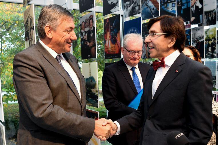 Vlaams minister-president Jan Jambon (N-VA) en zijn Waalse ambtsgenoot Elio Di Rupo  (PS) schudden elkaar de hand in het Groothertogdom Luxemburg. N-VA-communicatieman Pol Van Den Driessche kijkt toe.