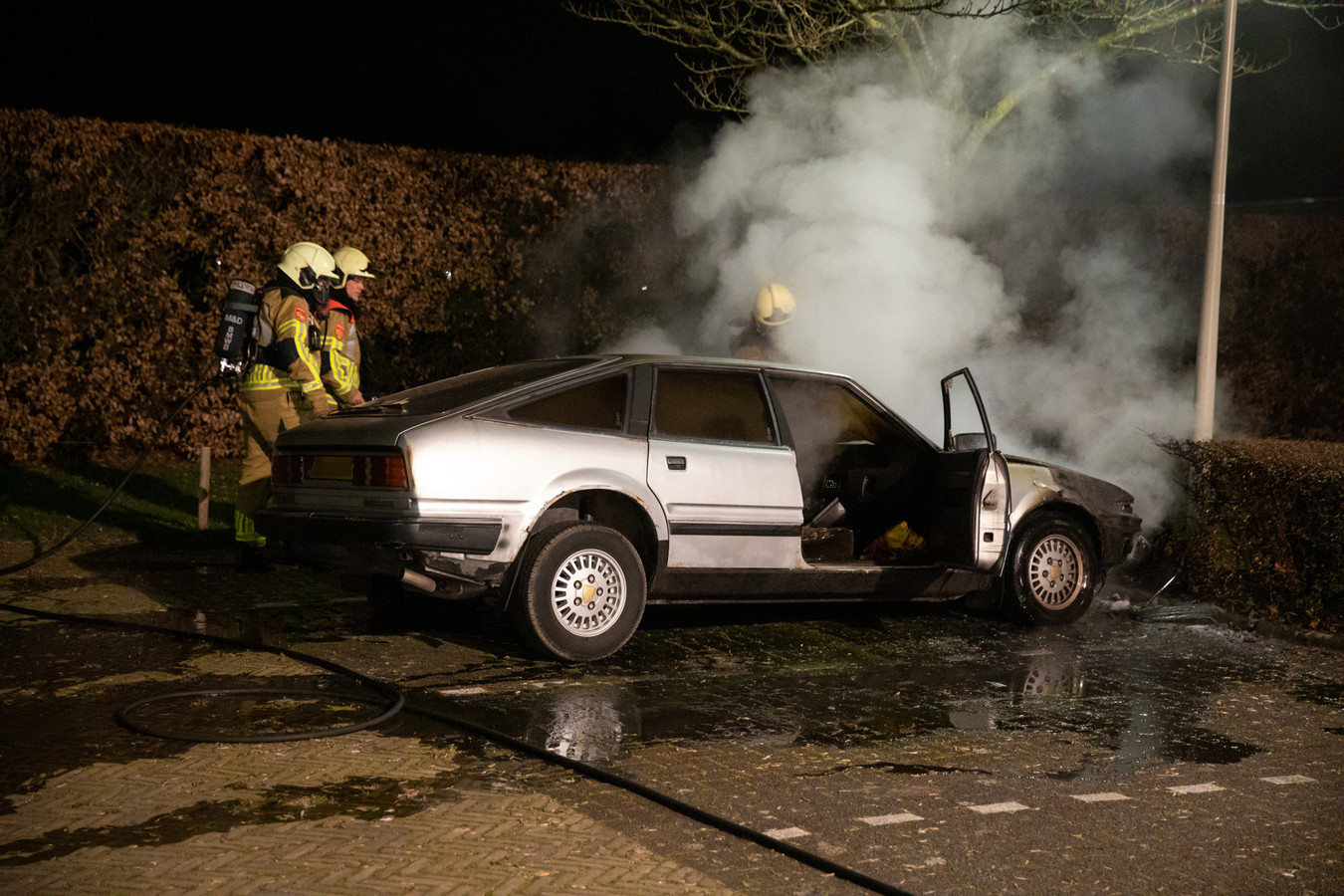 De brandweer blust de autobrand.