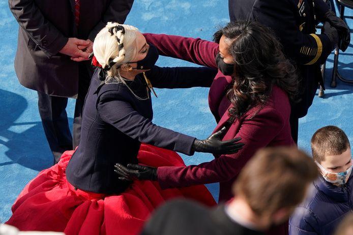 Lady Gaga en Michelle Obama op het punt om elkaar te omhelzen.