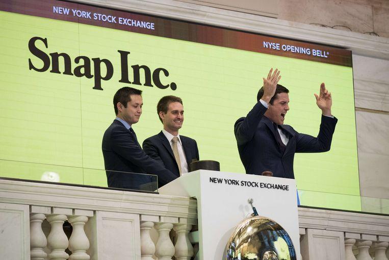 Snapchat-oprichters Bobby Murphy en Evan Spiegel samen met Thomas W. Farley, president van de New York Stock Exchange.  Beeld AFP