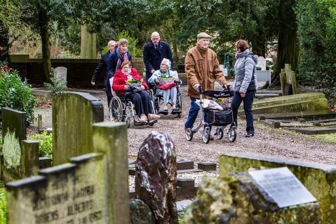 Zes ouderen worden door vrijwilligers begeleid naar het graf van hun geliefde.