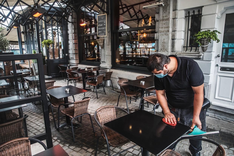 Een terrasje zonder volk in Antwerpen.De horeca stelt zelf een reeks strenge voorwaarden voor om weer volk te mogen ontvangen. Beeld Aurélie Geurts