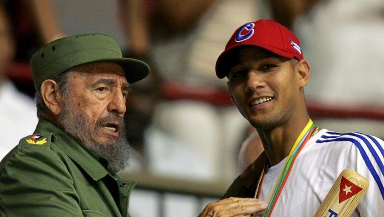 Toenmalig Cubaans president Fidel Castro overhandigt de Cubaanse baseballspeler Yulieski Gourriel een baseball bat. Beeld reuters