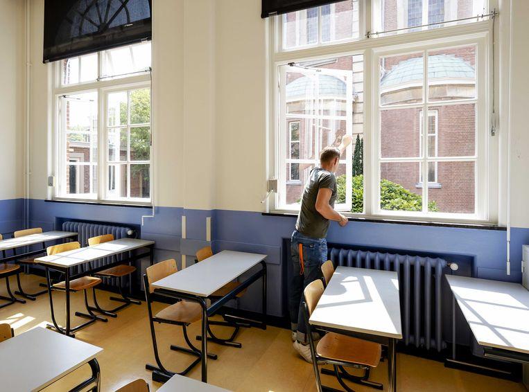 Een leraar zet de ramen open tijdens de voorbereidingen voor het begin van het nieuwe schooljaar.  Beeld ANP
