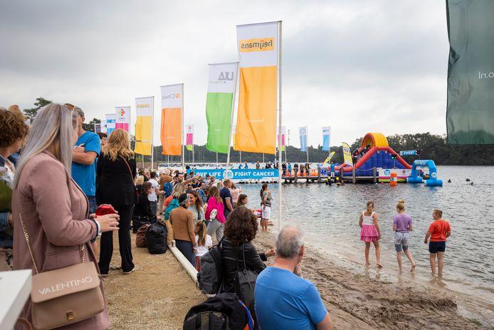 Op het strand van de IJzeren Man kijkt publiek naar de start en finish van Swim to Fight Cancer.