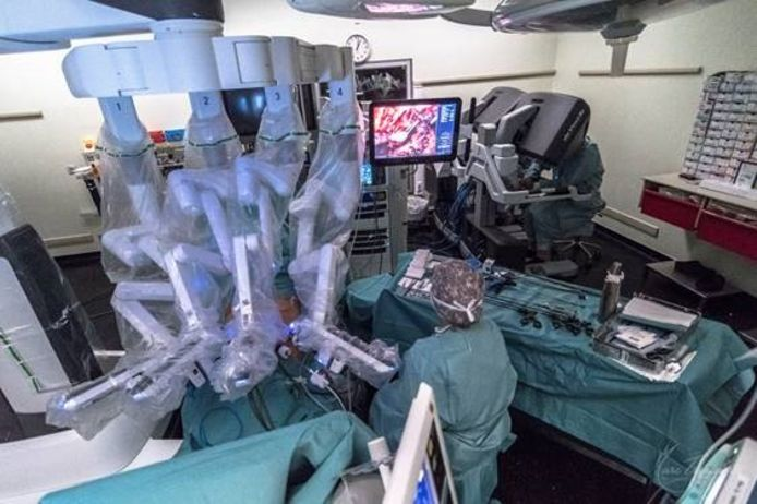 Le robot déployé sur le patient, l'écran de contrôle et les deux consoles pour les chirurgiens.