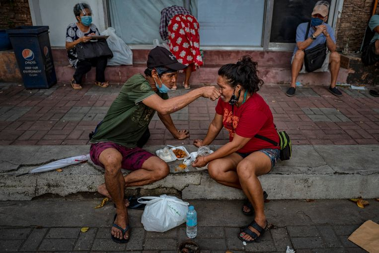 Daklozen in de Filippijnse hoofdstad Manila  krijgen een gratis maaltijd uitgereikt van de christelijke zendingsorganisatie Society of the Divine Word (SVD). Door de coronapandemie zullen dit jaar zeker 2,7 miljoen Filippino's extra onder de armoedegrens terechtkomen. Beeld Getty Images