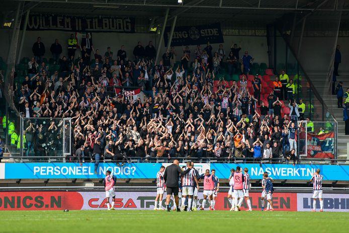 De spelers van Willem II vieren met de meegereisde fans het punt dat in Nijmegen uit het vuur gesleept is.