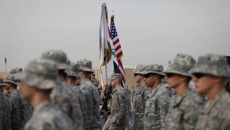 De Iraakse en Amerikaanse vlaggen worden naast elkaar gedragen Beeld ANP