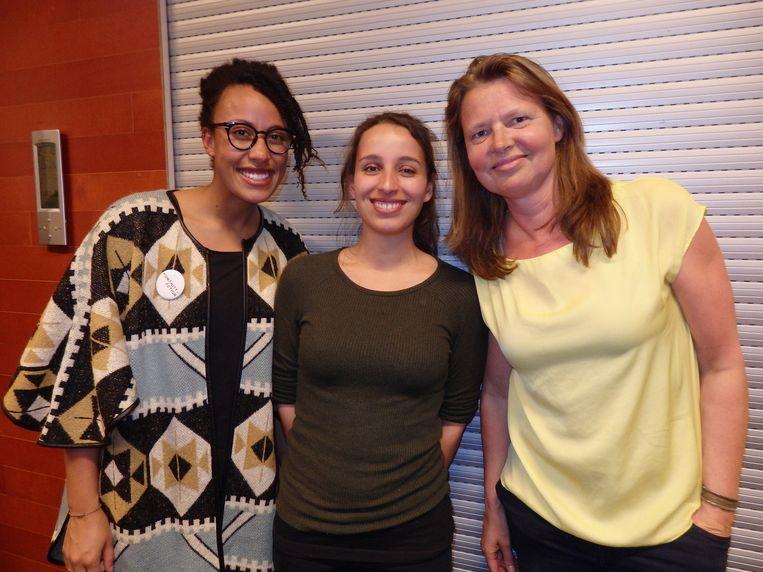Mavis Appiagyei, Eva Kassaye en Christel Groot (vlnr), van mede-organisator Humanity in action, delen cake uit. Beeld Schuim