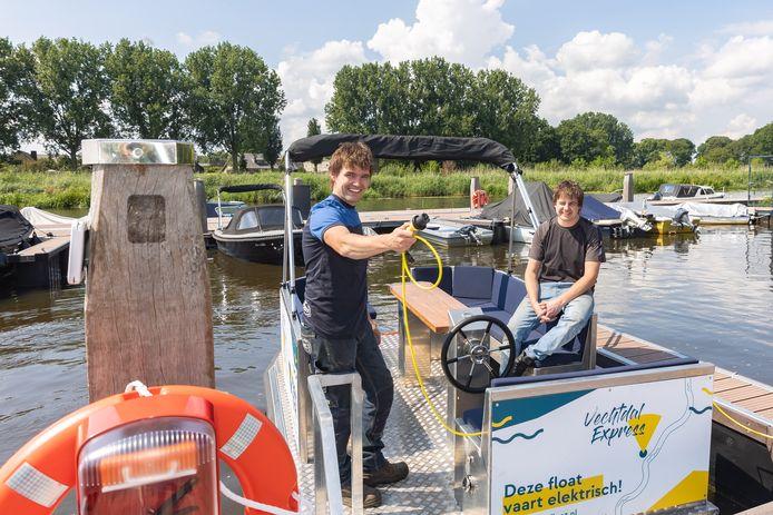 De Hardenbergse ondernemers Jelle Timmermans (rechts) en Gert Kremer op hun zelf ontworpen elektronische Vechtfloat in de haven van Hardenberg.