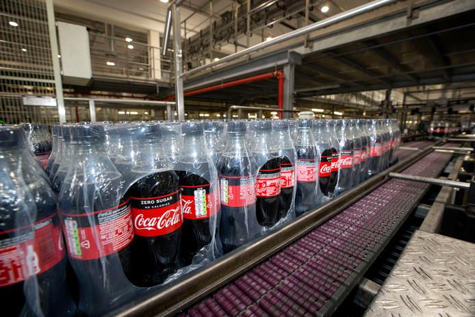 Coca-Cola-flessen ingepakt in plactic. Het bedrijf gaat het plastic rond blikjes in de fabriek in Dongen deels vervangen door karton.
