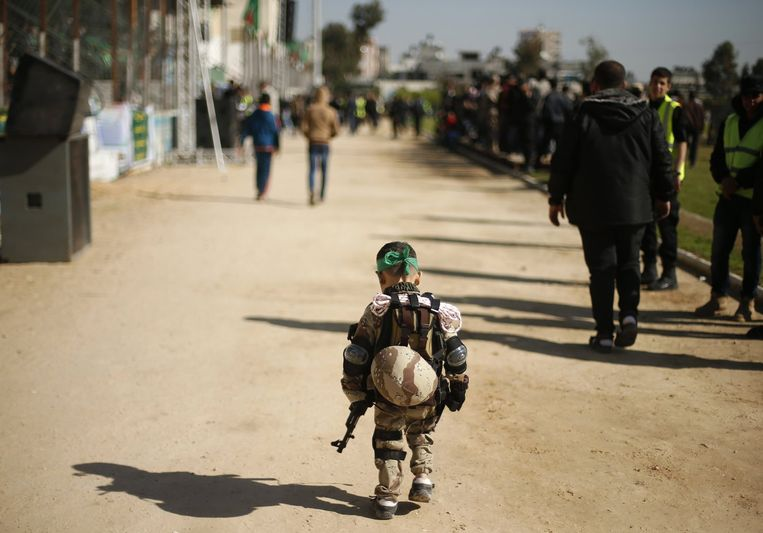Een Palestijns jongetje bij een afstudeerceremonie van een Hamaskamp, Gaza, januari 2015. Beeld Getty