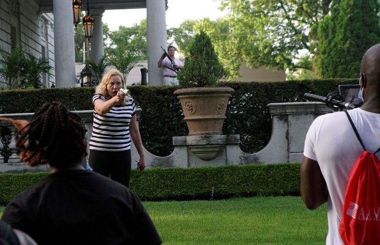 Patricia McCloskey richt haar wapen op demonstranten voor haar huis in Saint Louis tijdens een BLM-demonstratie. Beeld Reuters