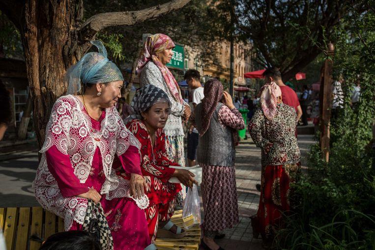 Oeigoerse vrouwen in traditionele klederdracht, in de regio Xinjiang in China. Beeld Getty Images