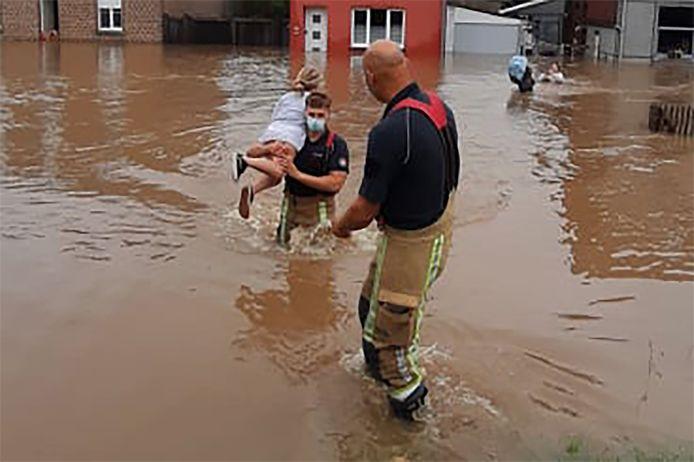 Brandweerlui haalden enkele mensen en kinderen uit de ondergelopen woningen.