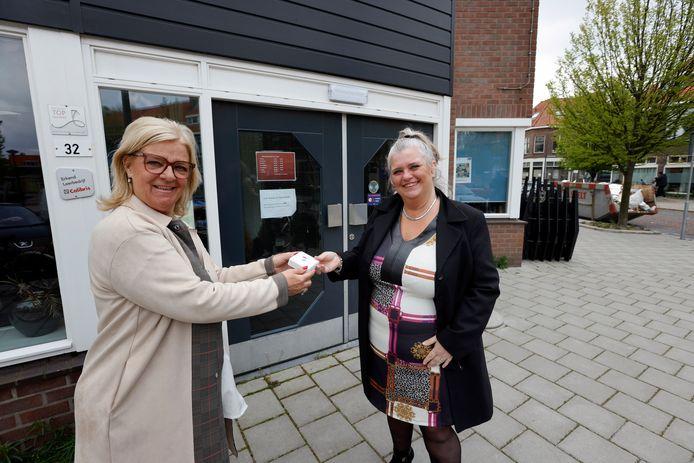 Mieke Wigmans (links) overhandigt de eerste behoeftelijnknop aan Ina Blans.