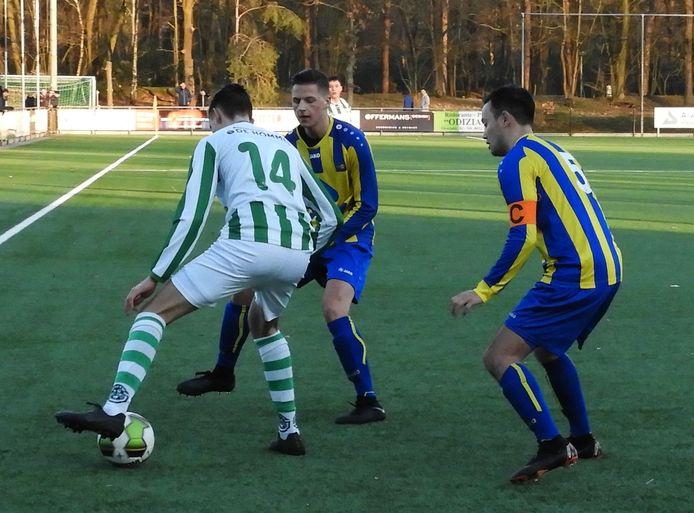 Sjors Bukkems (midden) namens Valkenswaard in duel met Rick van Heijnsbergen van Sparta'25. Rechts Sander Donkers.