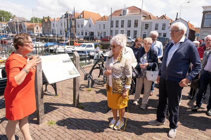 Gids Nannie Dorst geeft tijdens een stop in Brouwershaven de buspassagiers uitleg over het voormalig stadhuis.