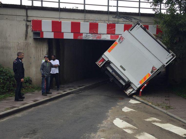 De vrachtwagen kwam schuin vast te zitten onder de lage spoorwegbrug.