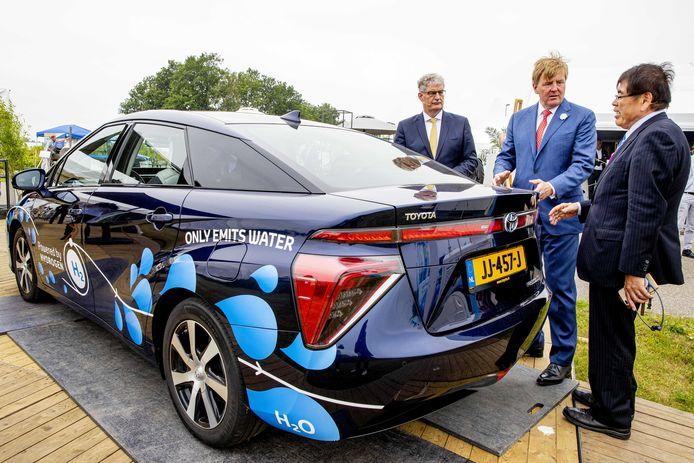 Koning Willem-Alexander laat zich bij de opening van de groene waterstofinstallatie HyStock van Gasunie bijpraten over de werking van een waterstofauto. I