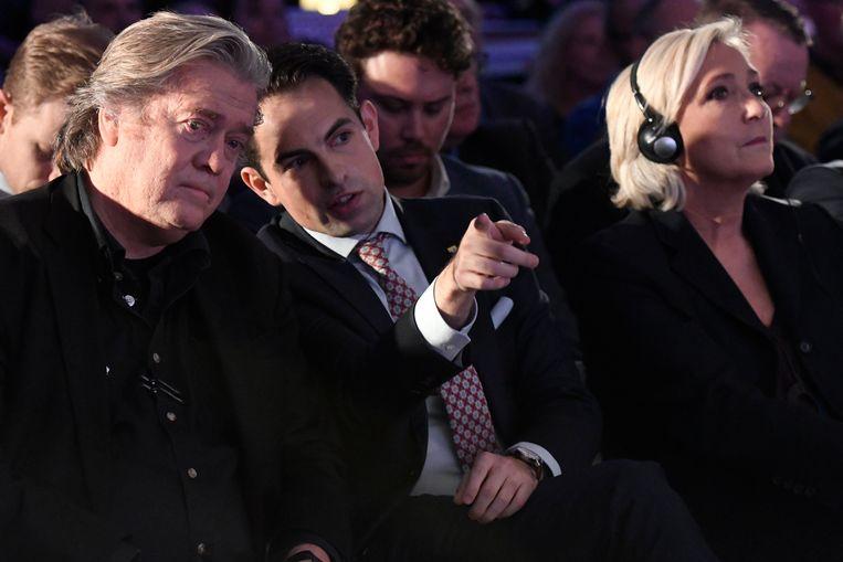 Steve Bannon (l.) en Tom Van Grieken (m.) naast Marine Le Pen, voorzitter van Rassemblement tijdens een evenement van Vlaams Belang tegen het VN-migratiepact. Beeld Photo News