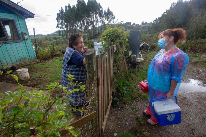 Verpleegster Ximena Ampuero op bezoek bij een oudere vrouw tijdens de vaccinatiecampagne in Chili.