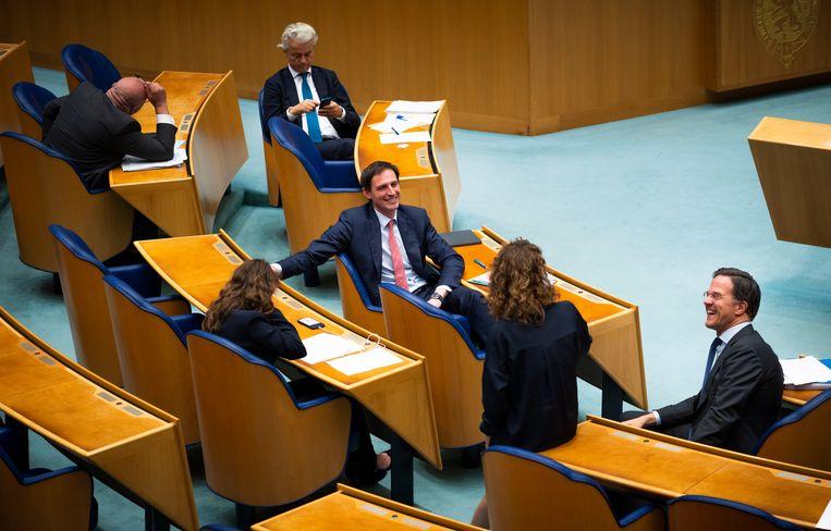 Wopke Hoekstra (CDA) in gesprek met Mark Rutte en Sophie Hermans (VVD) tijdens de schorsing van het debat over de formatie. Op de achtergrond Geert Wilders (PVV).  Beeld Freek van den Bergh / de Volkskrant