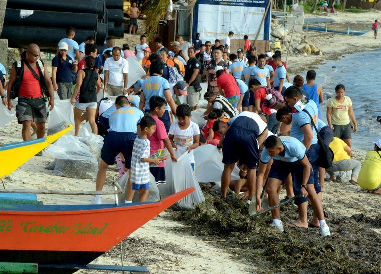 Vrijwilligers ruimen het Filipijnse eiland Boracay op, dat is sinds april 2018 gesloten voor toeristen.  Beeld EPA/Jo Haresh Tanodra