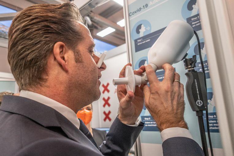 Minister Hugo de Jonge probeert de nieuwe blaastest.  Beeld Joris van Gennip