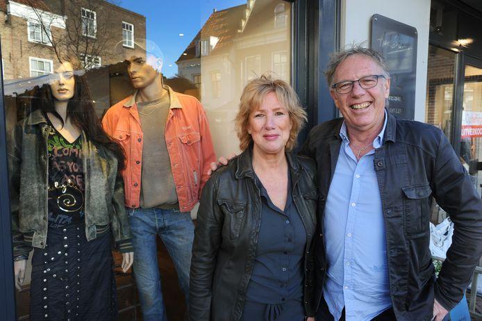 Anneke en Henk Sies voor hun modezaak met achter hen etalagepoppen, die kleren dragen die Anneke en Henk dertig, veertig jaar geleden zelf aan hadden.