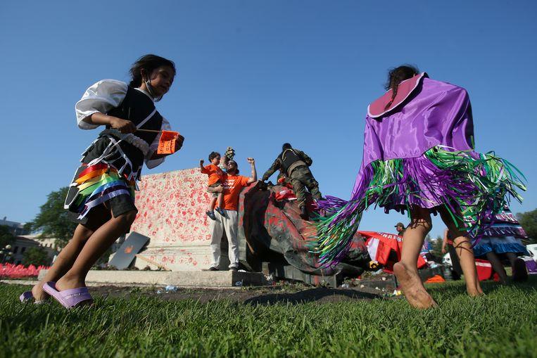 Demonstranten dansen rond een omvergetrokken beeld tijdens Canada Day in Winnipeg, Manitoba.  Beeld REUTERS
