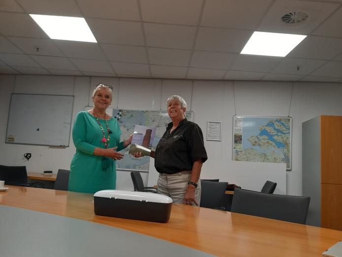 Wethouder Jacqueline van Burg (l) krijgt het eerste exemplaar van de glossy Erfgoed Schouwen-Duiveland van Ria Geluk, voorzitter van het Erfgoedplatform Schouwen-Duiveland.