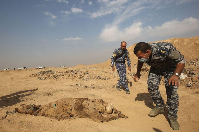 Leden van het Iraakse leger helpen de lichamen op te graven.
