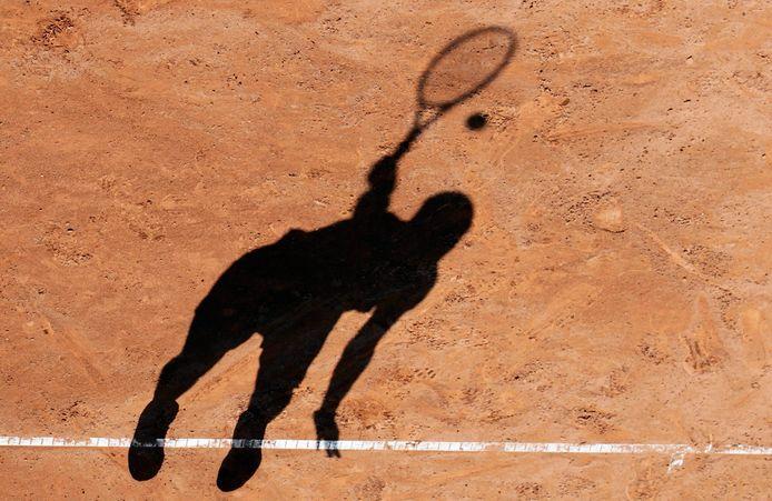 Een tennisster serveert op gravel.