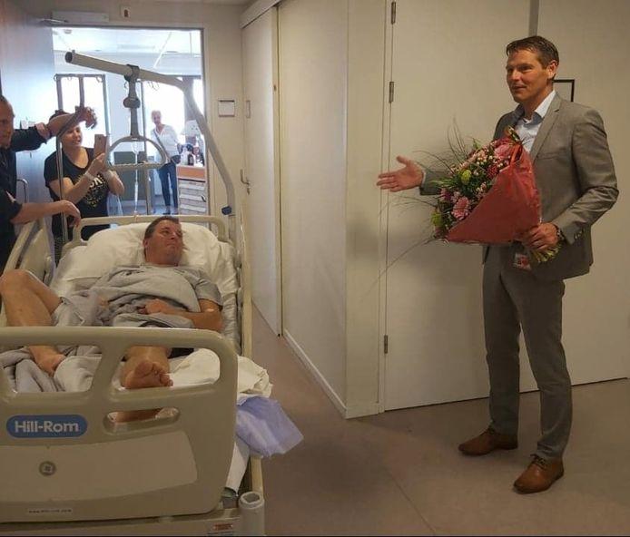 Martin van Hees wordt in het ziekenhuis verrast. Bestuursvoorzitter Langenbach van het Maasstad staat met bloemen voor hem klaar