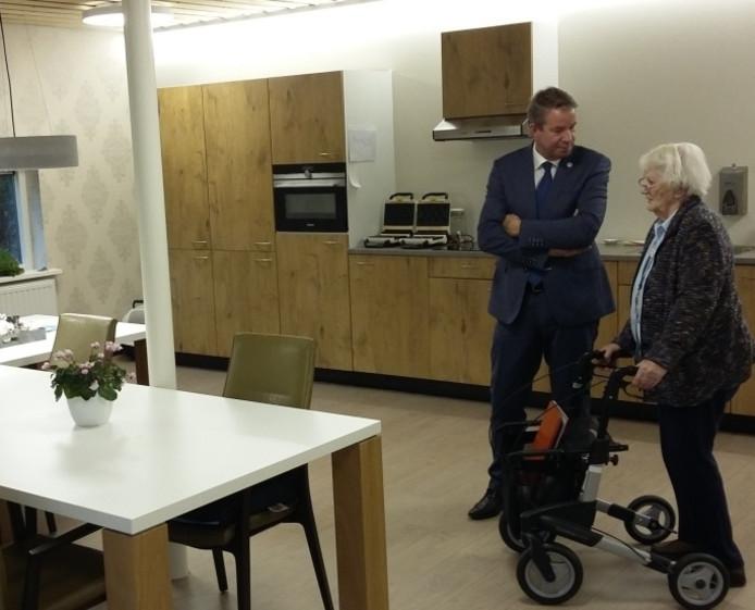 Truus Steketee leidt wethouder Albert Vader rond door de nieuwe huiskamer van zorgcentrum De Zoute Viever.