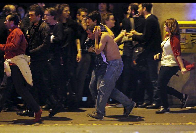 Mensen vluchten weg van de Bataclan concertzaal na de aanslagen in Parijs. Beeld reuters