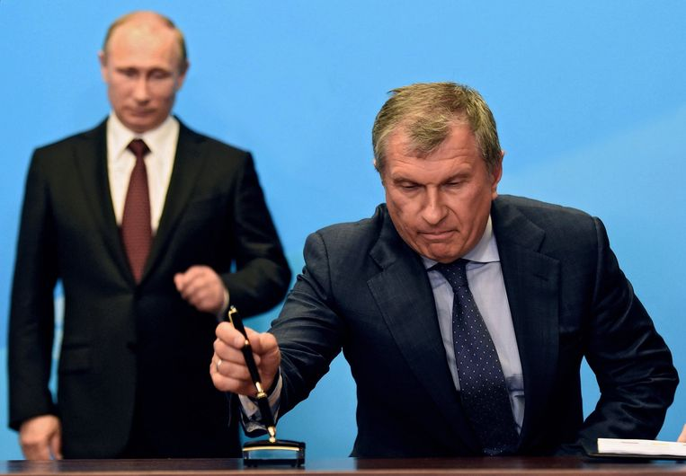 Rosneft-baas Igor Sechin doopt zijn pen onder het goedkeurend oog van Poetin. Beeld Photo News