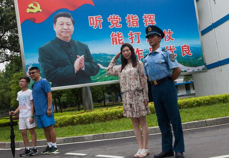 Een soldaat en enkele burgers poseren bij een afbeelding van president Xi Jinping, Hong Kong 2017. Beeld EPA