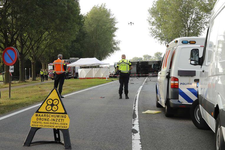 De politie heeft de weg afgezet in het Brabantse Escharen waar een Nederlander die  in Roemenië werd gezocht wegens een misdrijf om het leven is gekomen door een auto-ongeluk. De 46-jarige man zou betrokken zijn bij de dood van een Roemeens meisje van 11 jaar.  Beeld ANP