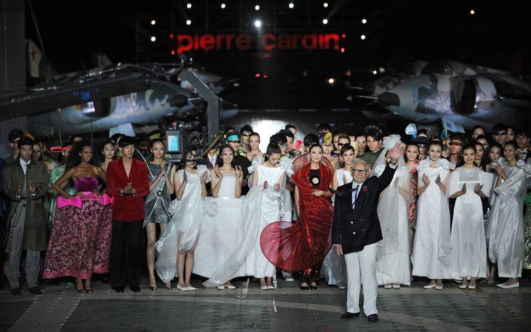 Pierre Cardin bedankt in 2011 het publiek dat aanwezig was bij zijn modeshow op een vliegdekschip in de haven van Tianjin, China. Beeld AFP