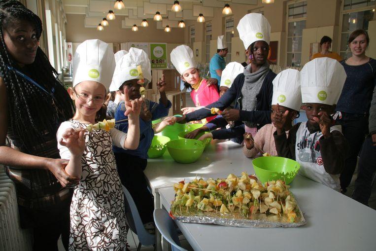 De kinderen van het asielcentrum maken fruitbrochettes.