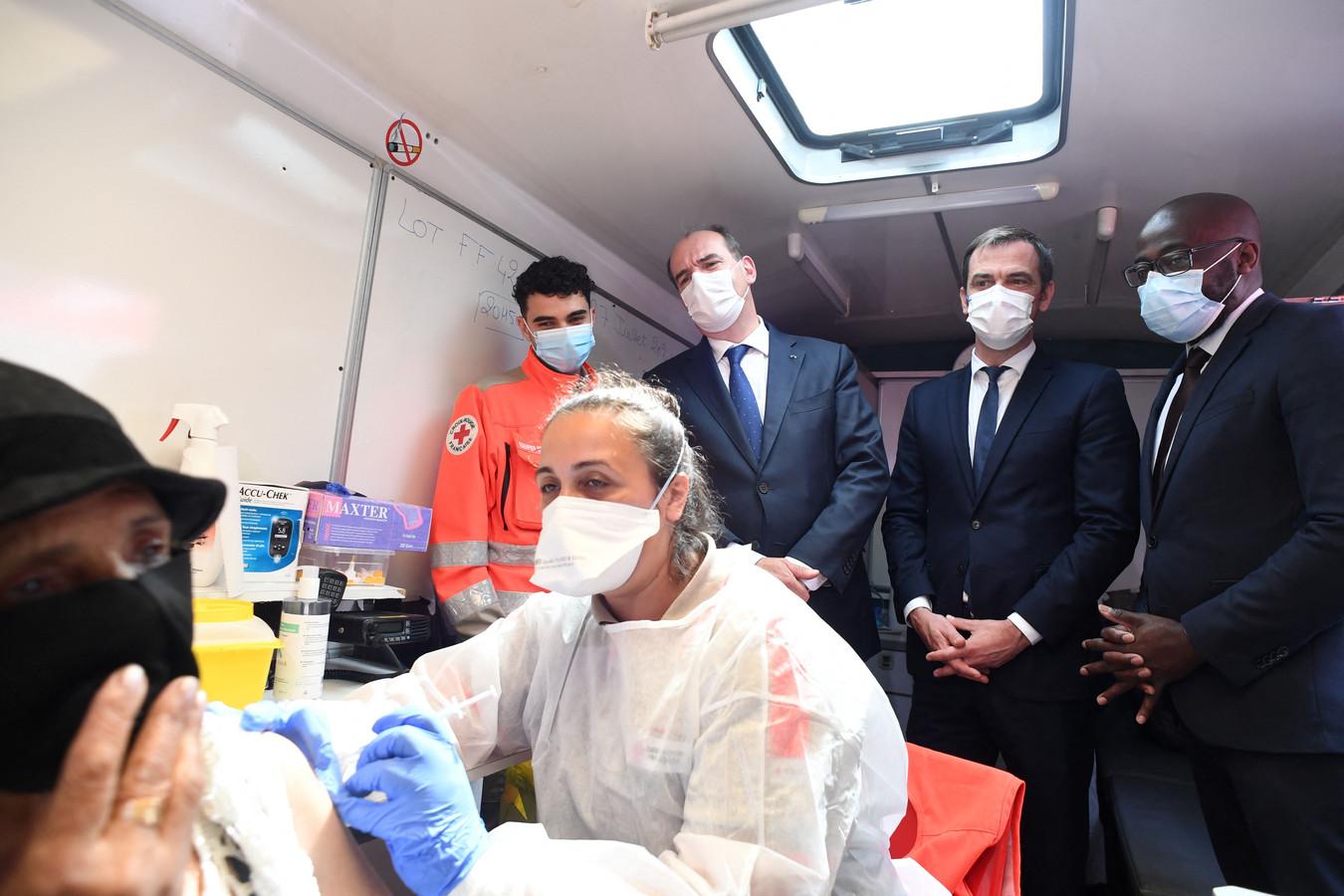 De Franse minister van Volksgezondheid Olivier Veran en premier Jean Castex kijken in Parijs toe hoe een coronavaccin toegediend wordt.