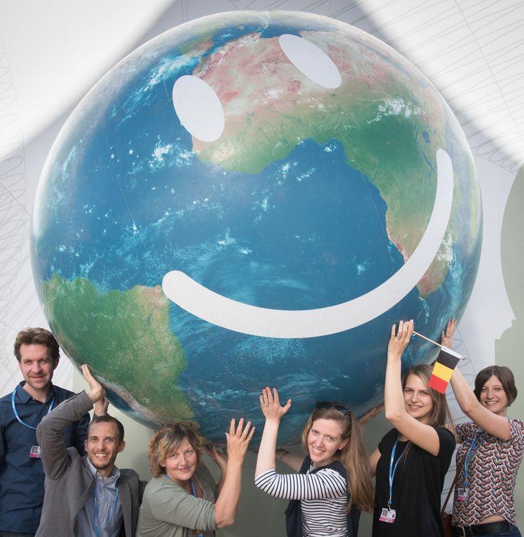 Belgische ngo-medewerkers houden een opblaasbare wereldbol de lucht in op de klimaatconferentie in Marrakech. Beeld BELGA